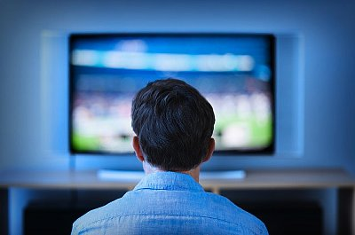 Jersey City, New Jersey, USA --- Jersey City, New Jersey, Man watching tv in living room --- Image by © Tetra Images/Corbis